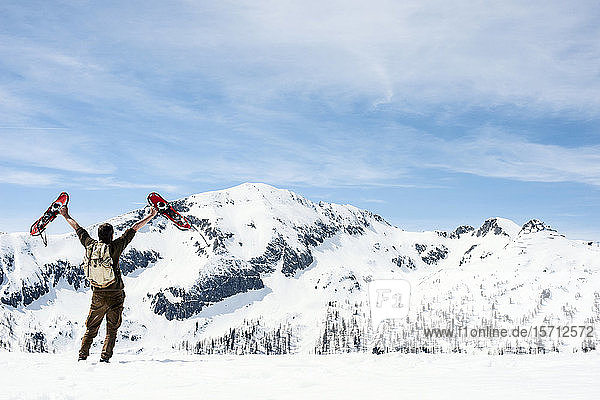 Mann mit Rucksack  auf Berggipfel stehend  winkt mit seinen Schneeschuhen  Rückansicht  Bundesland Salzburg  Österreich