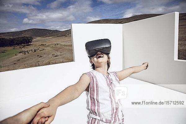 Mädchen schaut durch eine VR-Brille im offenen Raum