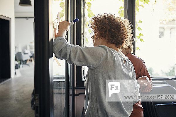 Kollegen schreiben auf Haftnotizen an einer Glasscheibe im Büro