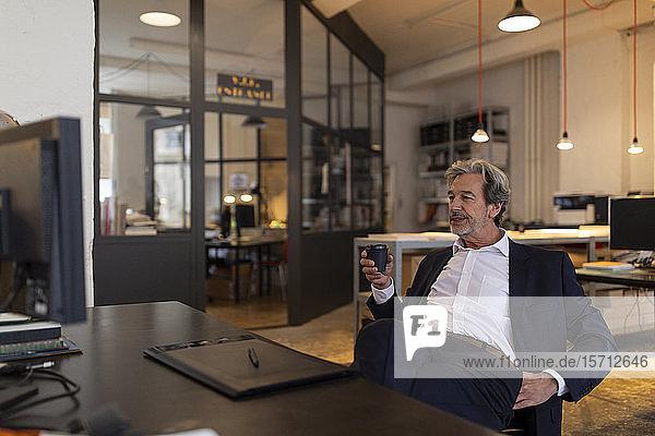 Entspannter leitender Geschäftsmann sitzt im Büro am Schreibtisch