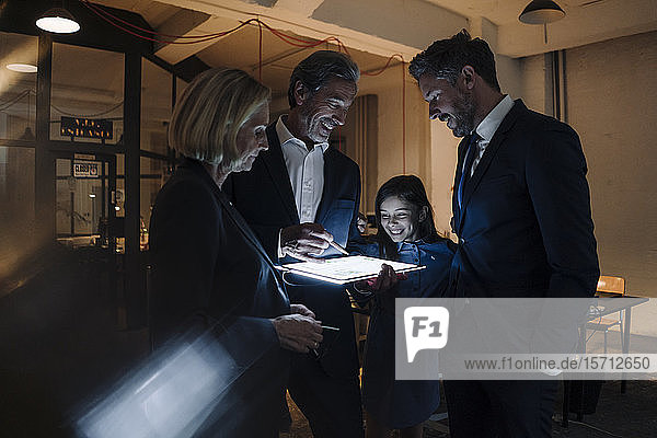 Happy business people and girl looking at shining tablet in office