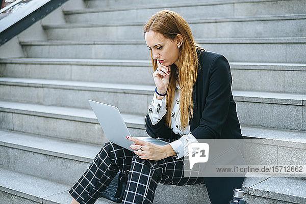 Junge Geschäftsfrau sitzt mit Laptop auf der Treppe