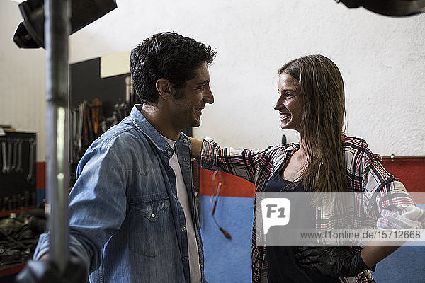 Side view of young smiling woman and man looking at each other while standing in car repair service and communicating