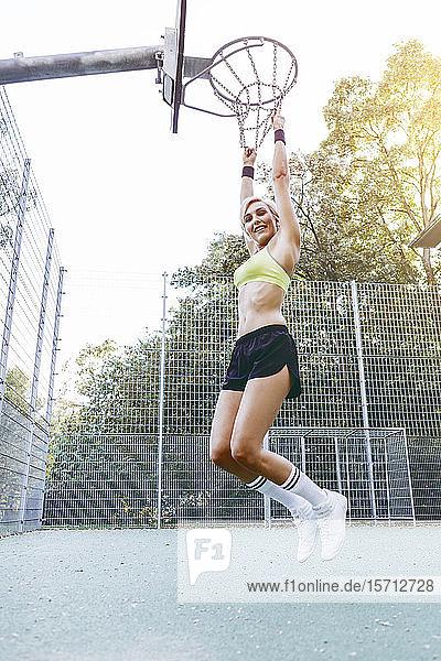 Blonde Frau spielt Basketball  am Korb hängend