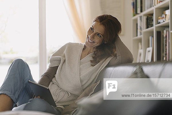 Lächelnde Frau sitzt auf dem Sofa und benutzt ein digitales Tablett