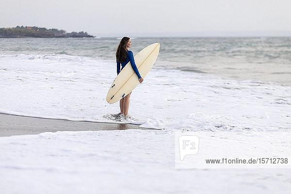 Junge Frau mit Surfbrett am Strand  Strand von Kedungu  Bali  Indonesien