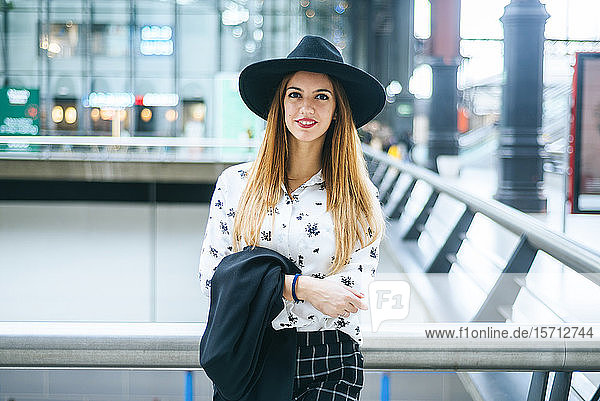 Portrait of smiling young woman wearing a hat at train station