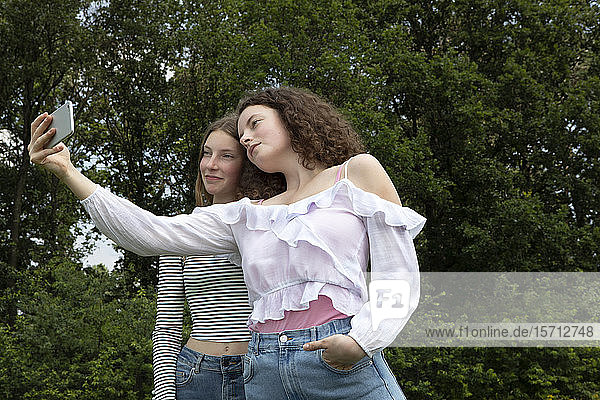 Two best friends taking selfie with smartphone in nature