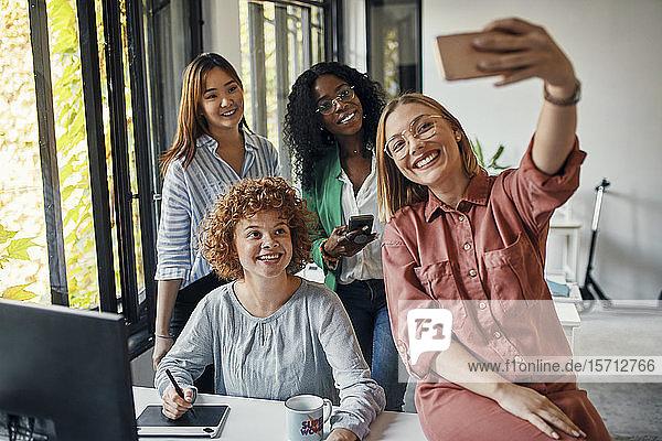 Happy female colleagues taking a selfie in office
