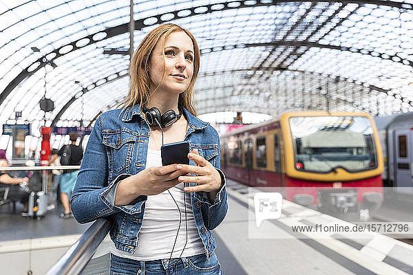 Lächelnde Frau mit Smartphone und Kopfhörern auf dem Bahnsteig  Berlin  Deutschland