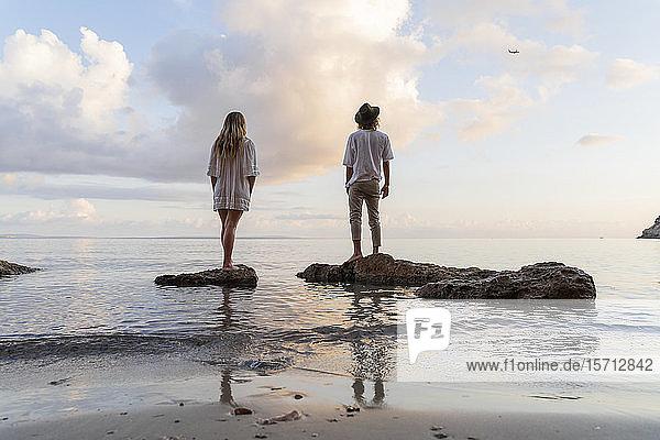 Rückenansicht eines jungen Paares  das auf Felsen vor dem Meer steht und ein Flugzeug beobachtet  Ibiza  Balearen  Spanien