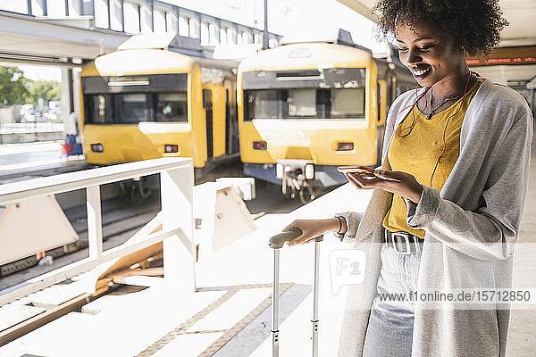 Lächelnde junge Frau mit Kopfhörern und Smartphone am Bahnsteig