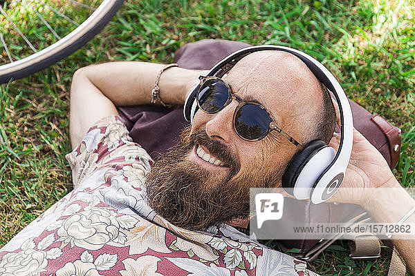 Mature man with red basecap  sunglasses and white headphones