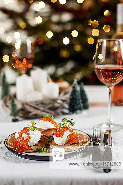 Blinis mit Sauerrahm  Räucherlachs und Fischrogen  vor Weihnachtsdekoration