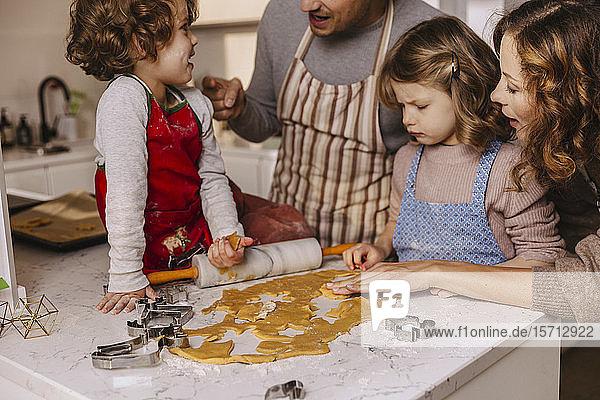 Familie bereitet Weihnachtsplätzchen in der Küche zu