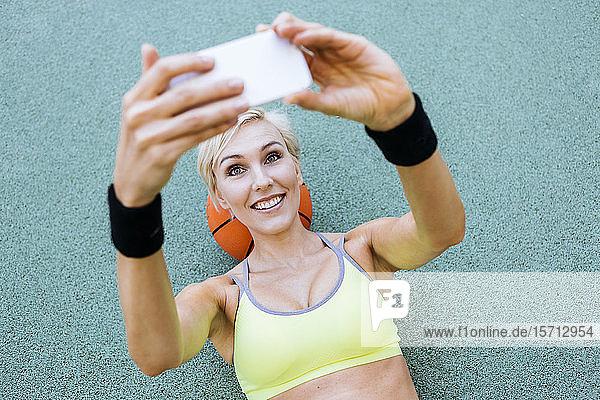 Blonde Frau liegt auf Basketball und nimmt ein Selfie