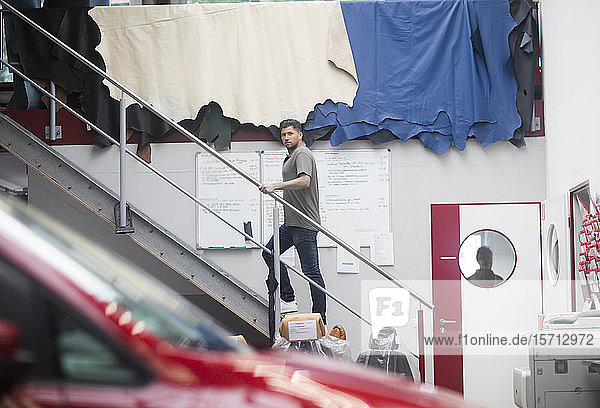 Junger Mann bei der Arbeit in einer Polsterei  Treppensteigen