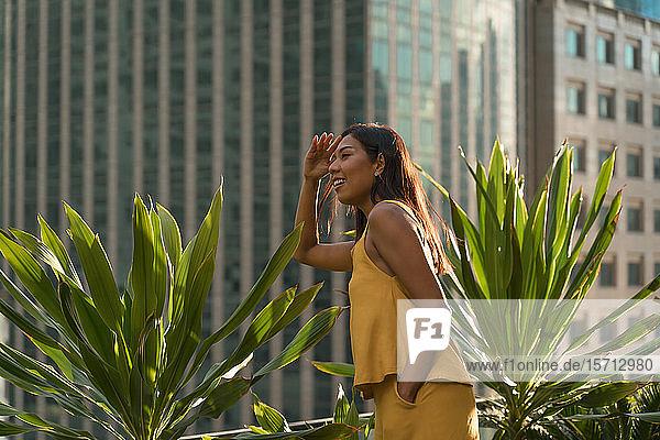 Lächelnde Frau steht auf der Dachterrasse und schaut in die Ferne  Bangkok  Thailand