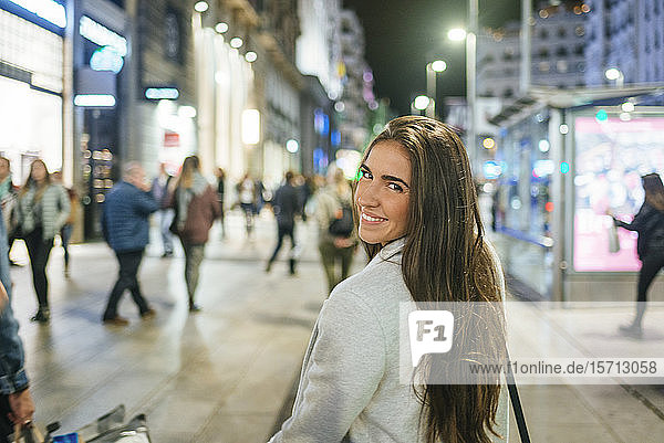 Portrait of a smiling woman walking down shopping street at night