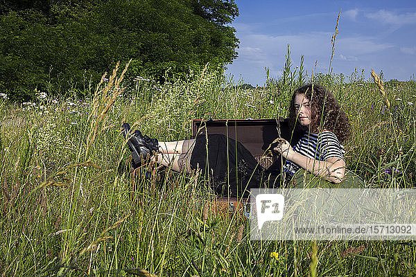 Portrait of young woman sitting in suitcase on a meadow