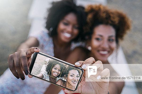 Junge Frauen,  die lächeln und sich mit ihrem Smartphone in einem Park ein Selfie machen