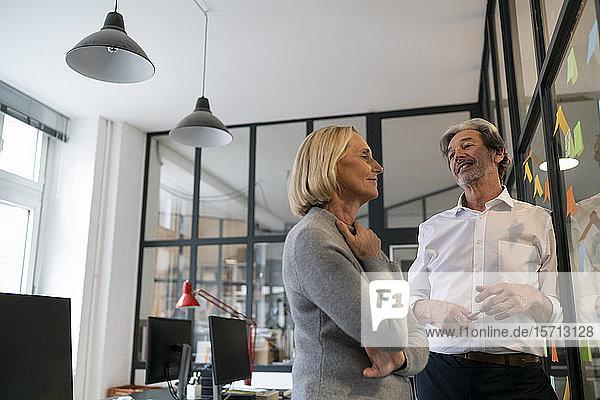 Geschäftsmann und Geschäftsfrau arbeiten an Haftnotizen an einer Glasscheibe im Büro