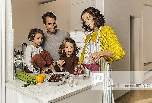 Mutter bereitet in der Küche einen Smoothie für ihre Familie zu