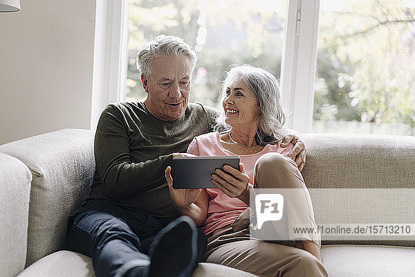 Happy senior couple relaxing on couch at home using tablet