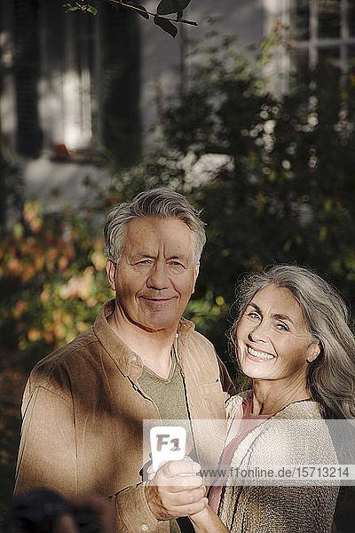 Portrait of happy senior couple in garden of their home in autumn