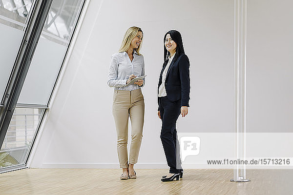 Two businesswomen with tablet standing in modern office