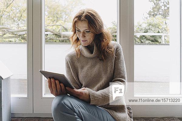 Eine reife Frau sitzt auf einer Schwelle und benutzt ein digitales Tablett