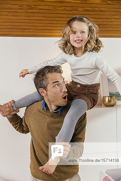 Happy father carrying daughter on shoulders at home