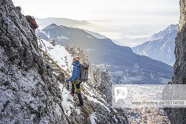 Alpinist standing in a rocky snowy mountain looking up  Orobie Alps  Lecco  Italy