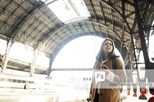 Junge Frau mit Handy am Bahnhof  die sich umsieht