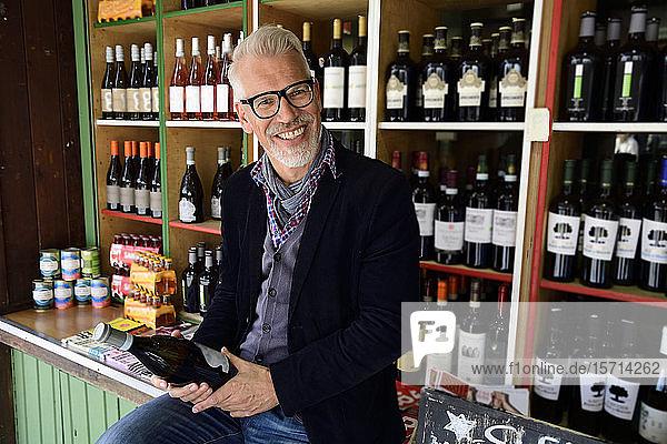 Porträt eines lächelnden reifen Mannes bei der Auswahl einer Flasche Wein in einem Weinladen