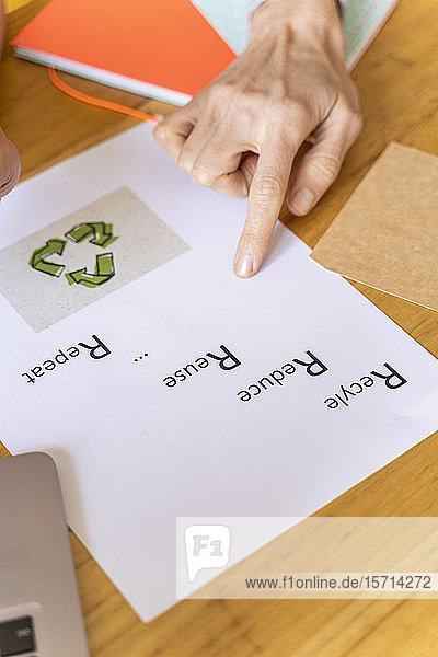 Businesswoman pointing on paper with recycling symbol in office