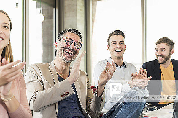 Happy business people applauding during a meeting in boardroom