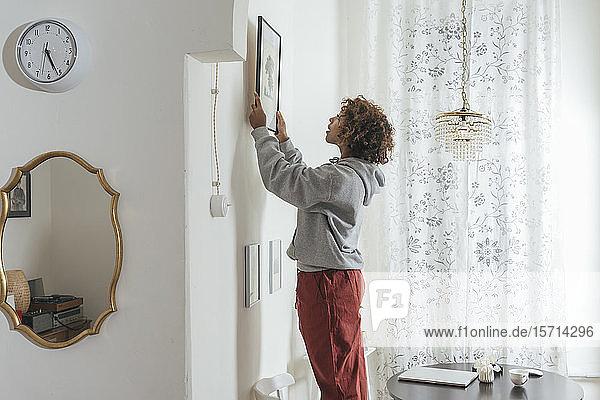 Junge Frau hängt zu Hause ein Bild auf