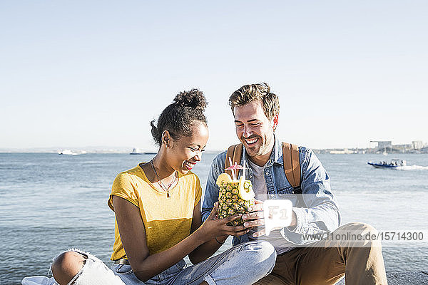 Happy young couple sitting at the waterfront sharing a drink in a pineapple  Lisbon  Portugal