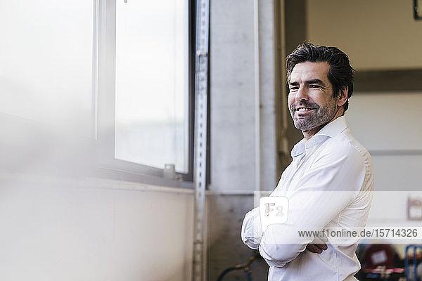 Porträt eines lächelnden Geschäftsmannes am Fenster in einer Fabrik