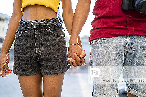 Nahaufnahme eines jungen Paares Hand in Hand im Freien Nahaufnahme eines jungen Paares Hand in Hand im Freien