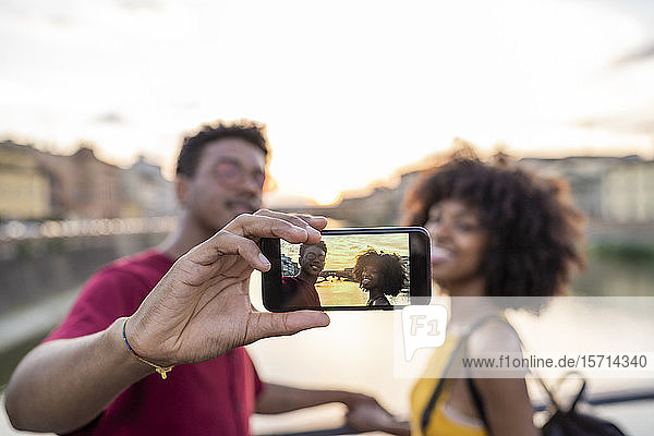 Young tourist couple taking a selfie on a bridge above river Arno at sunset  Florence  Italy