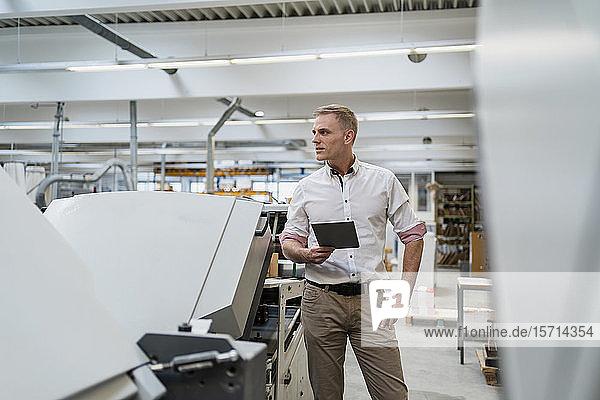 Geschäftsmann mit einer Tablette in einer Fabrik  der sich umsieht