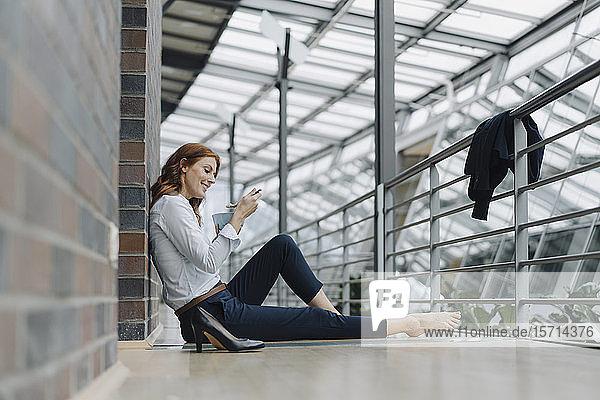 Geschäftsfrau sitzt im Büro auf dem Boden und isst Müsli