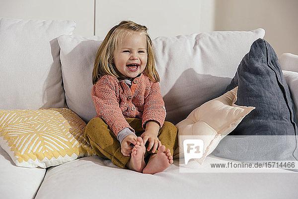 Lachendes kleines Mädchen sitzt zu Hause auf dem Sofa
