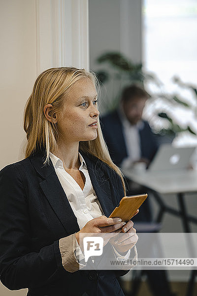 Young businesswoman with cell phone in office