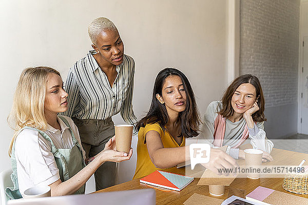 Businesswomen having a meeting in office working on reusable cups