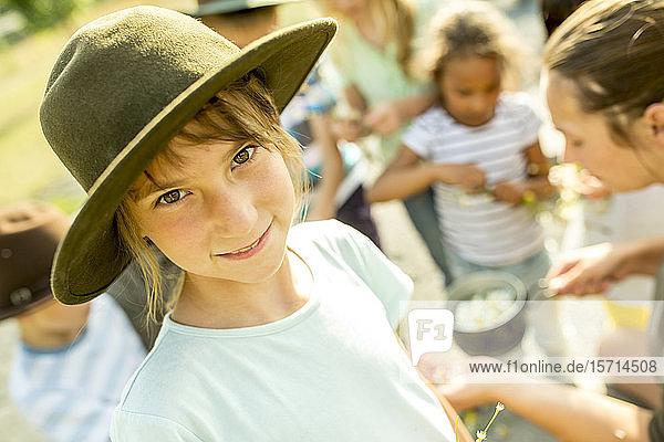 Schulkinder lernen  wie man einen Kamillenaufguss zubereitet  Mädchen lächelt in die Kamera