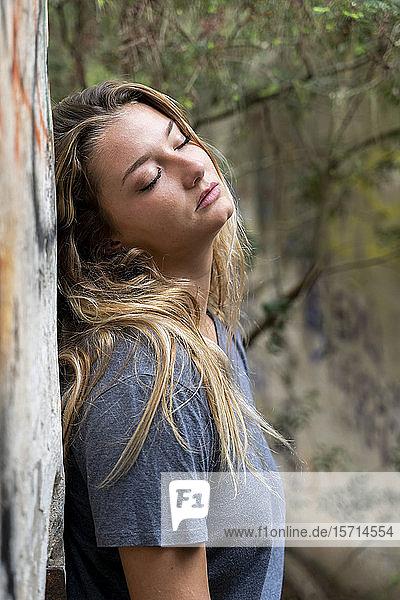 Junge blonde Frau  die an einer Wand lehnt  mit geschlossenen Augen