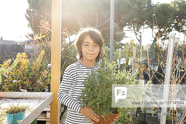 Portrait of boy with potted plant at plant nursery